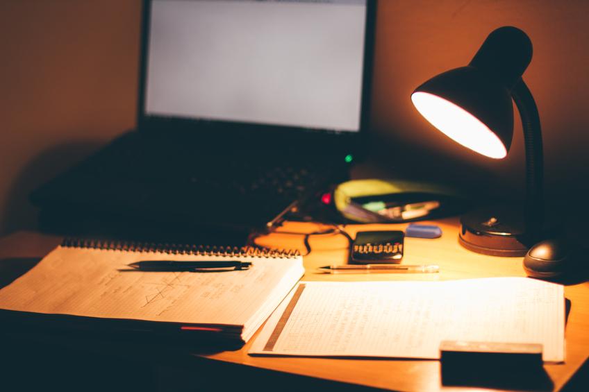 Obrázok počítača na pracovnom stole pri zasvietenej lampe.