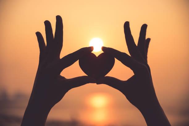 Dve ruky, ktoré držia v prstoch srdiečko počas západu slnka..
